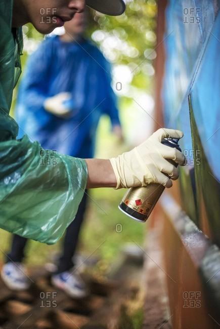 Close-up Of Young Man Spraying Paint On A Graffiti Wall