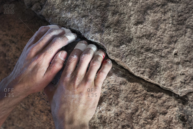 Bloodied And Taped Up Climber's Hands Grab A Chalked Up Crack