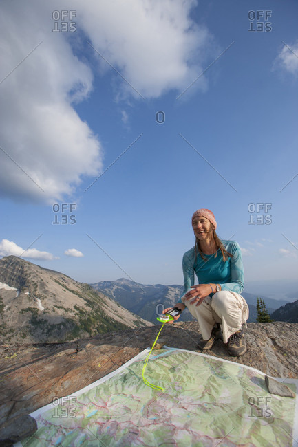 An Adult Woman Squatting Down By A Map In The Cabinet Mountains In Idaho
