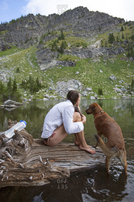 A Woman And Her Dog Sitting On A Drift Log After A Swim In A High Mountain Lake