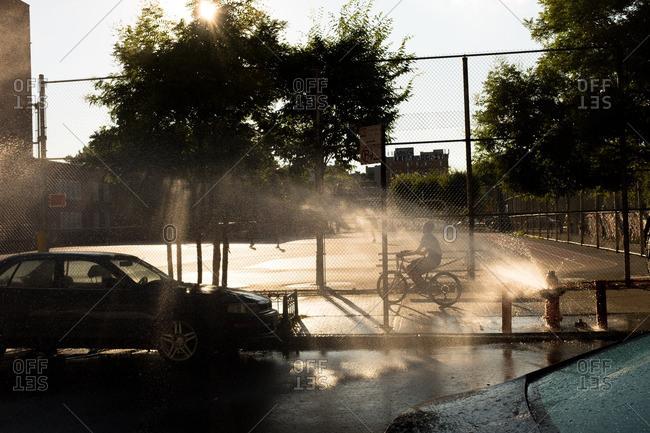 August 4, 2015 - Brooklyn, New York: Boy riding bike past fire hydrant spray on summer day