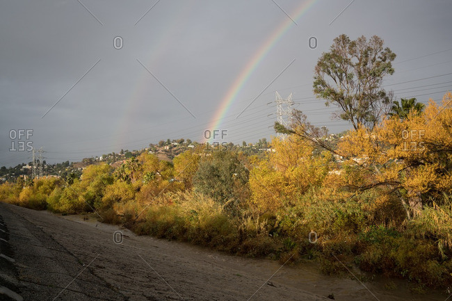 Double rainbow in dark sky over gritty urban landscape