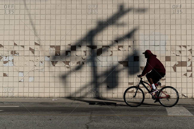 Man on bicycle silhouetted against tiled wall