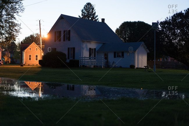 Puddle in lawn of farm house at dusk