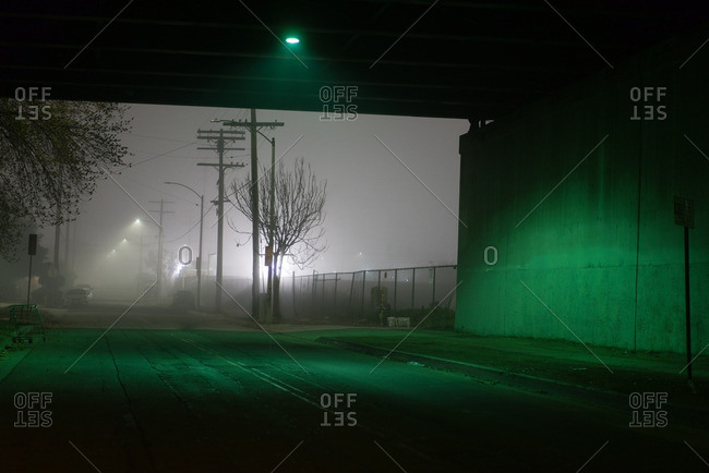 Road beneath bridge lit by green light on foggy night