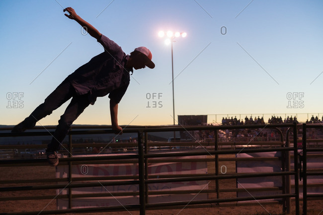 July 22, 2016 - Driggs, Idaho: Silhouetted teen leaping over fence at rodeo corral