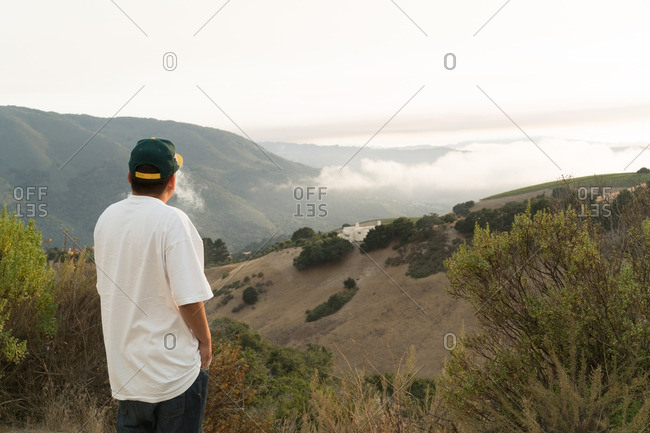 Man overlooking foggy hillside with luxury home