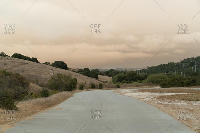 Road through desert hills under cloudy skies