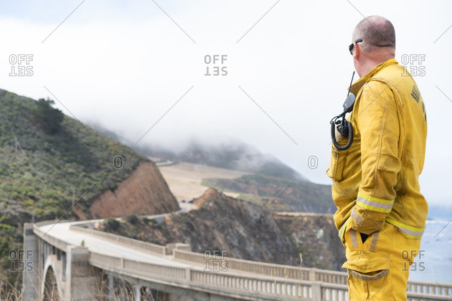 July 31, 2016 - Big Sur, California: Firefighter helping battle the Soberanes wildfire overlooking bridge and ocean