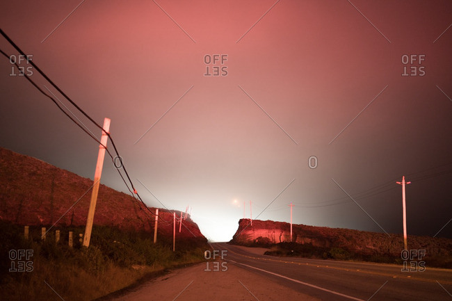 Desert road and power lines at sunset