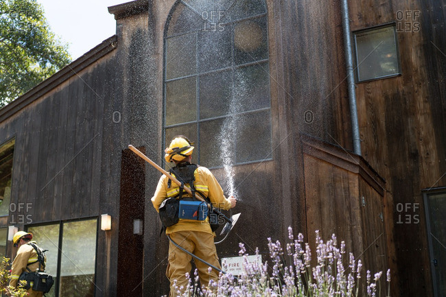 July 31, 2016 - Big Sur, California: Firefighter spraying house to minimize risk from the Soberanes wildfire
