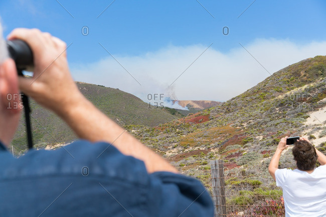 People watching wildfires spreading in distance