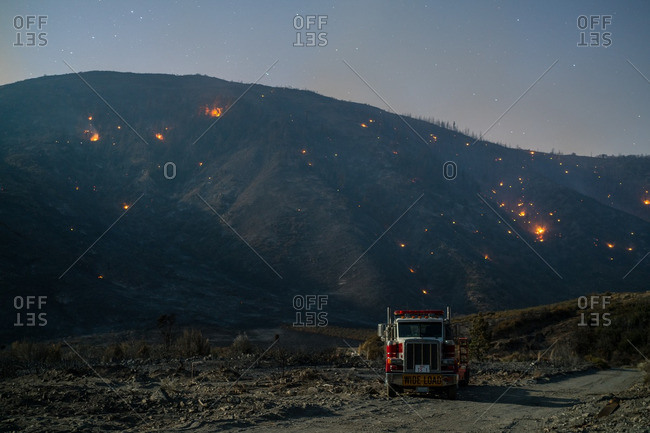 August 18, 2016 - Wrightswood, California: Embers from the Blue Cut fires glow in hills above fire truck