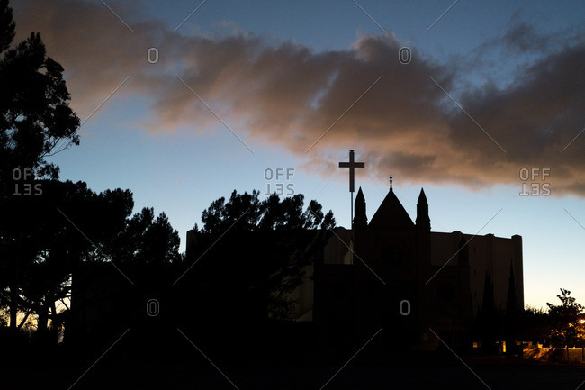 Church building silhouetted at sunset