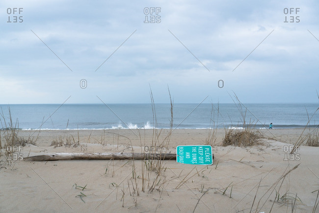 Fallen sign warning to keep off dunes on beach