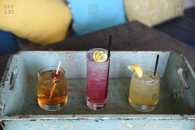 Three cocktails on wood tray