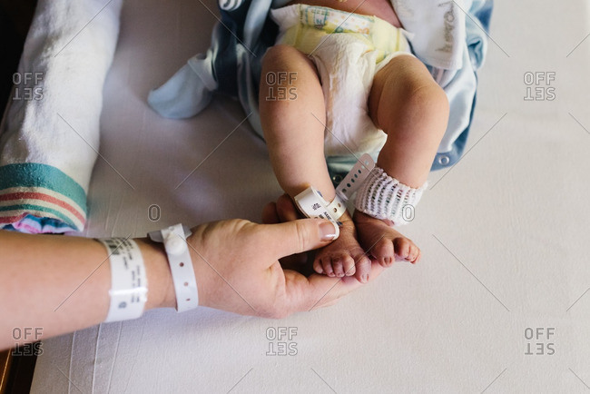 Mother's hand touching newborn's foot