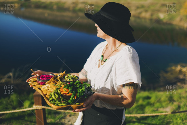 Woman with tray of food in countryside