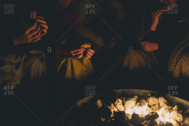 People eating around campfire at night