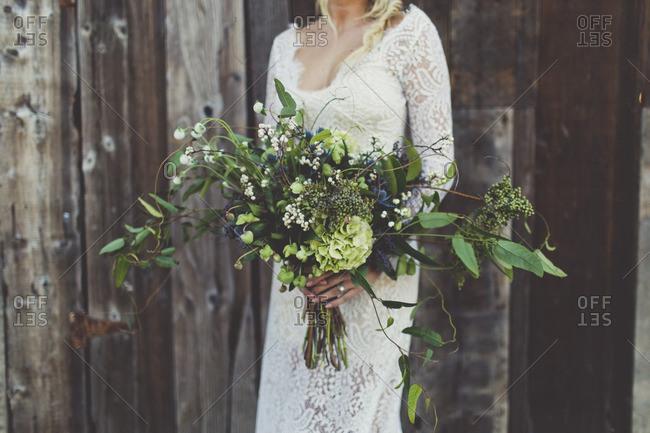 Bride holding wide flower bouquet