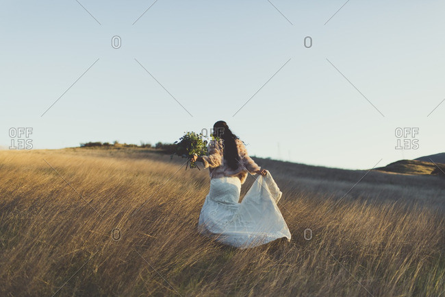 Bride in a fur coat walking in hills