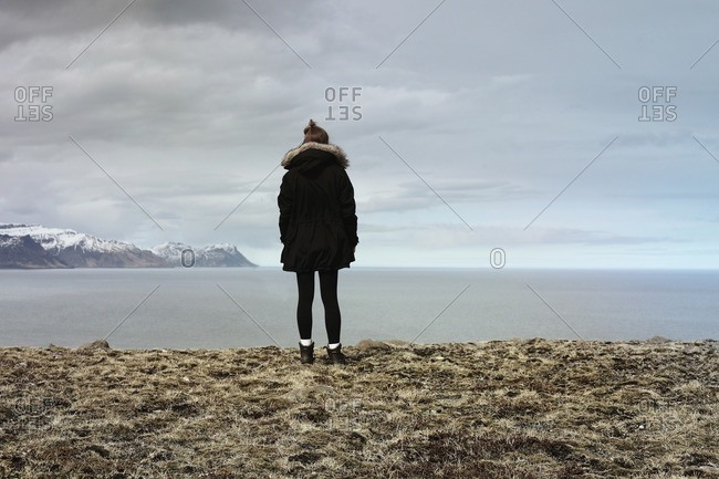 Young woman looking out over fjord in Iceland