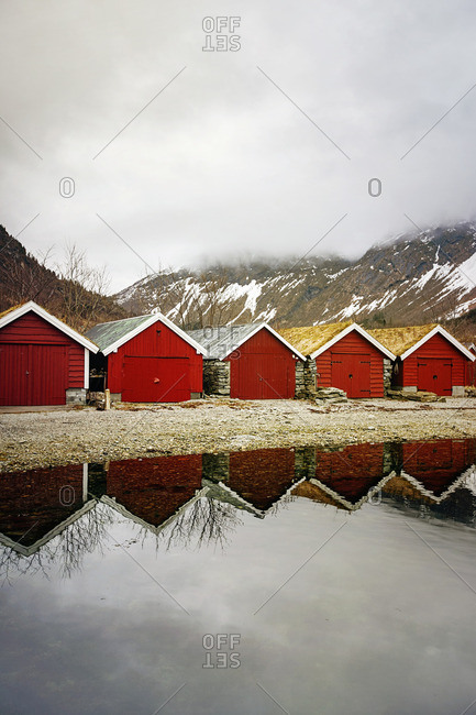 Row of red houses reflected in water in Norway
