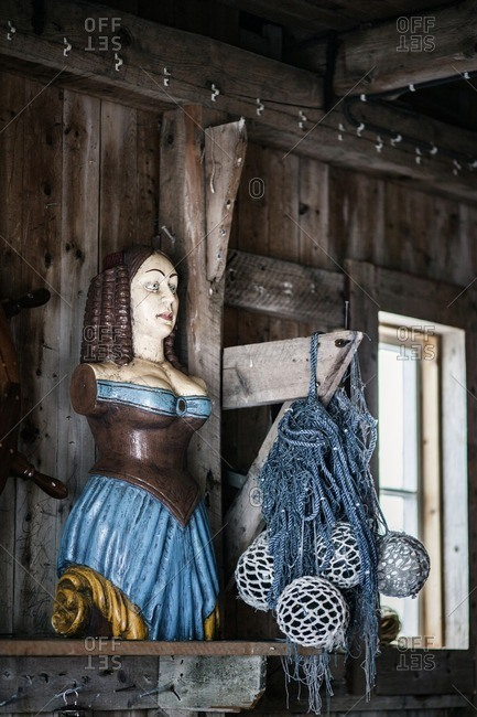 Nautical decorations of figurehead and glass fishing floats on display
