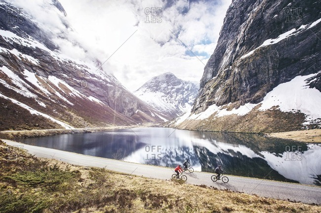 Sunnmore, Romsdal, Norway - January 7, 2017: People riding bikes on road alongside fjord and mountains