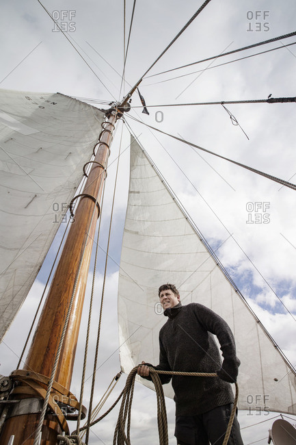 Alesund, Norway - April 16, 2016: Man holding ropes on training ship