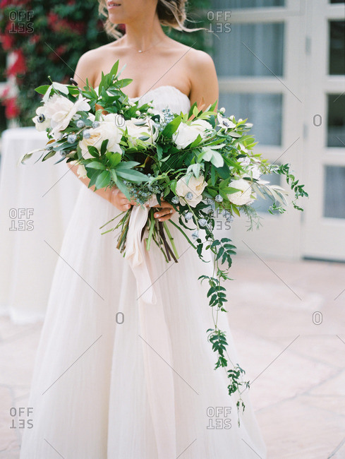 Neck down portrait of seated bride with white and green floral bouquet