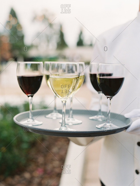 Serving holding tray with glasses of white and red wine