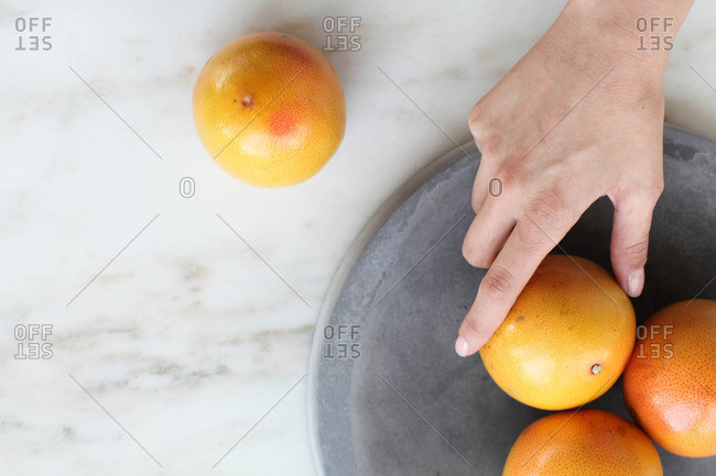 Overhead view of hand reaching for grapefruit