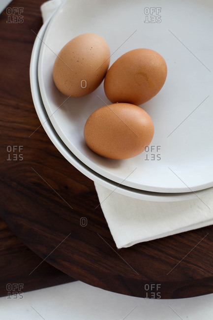 Three brown eggs on a white plate