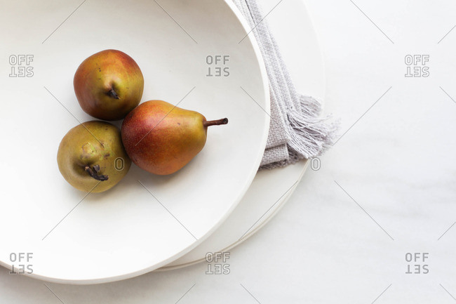 White plate with three fresh pears