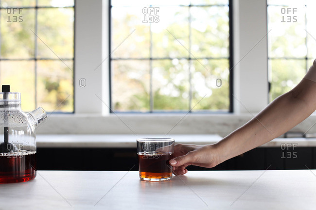 Person with cup of tea in kitchen