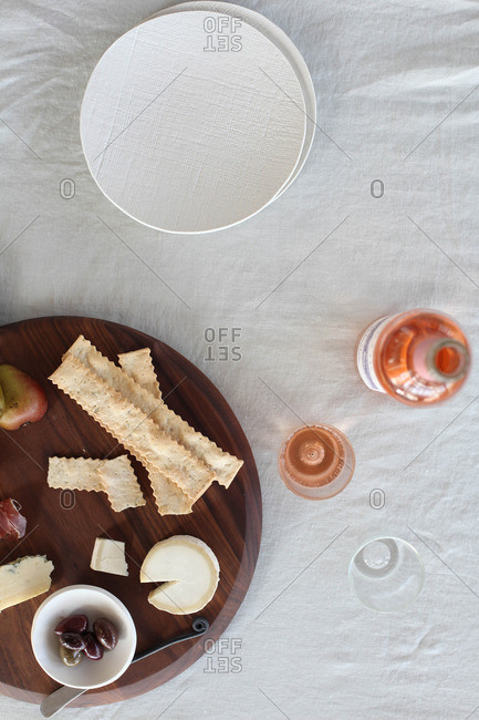 Plate of cheese, ham, olives and crackers served with rose wine