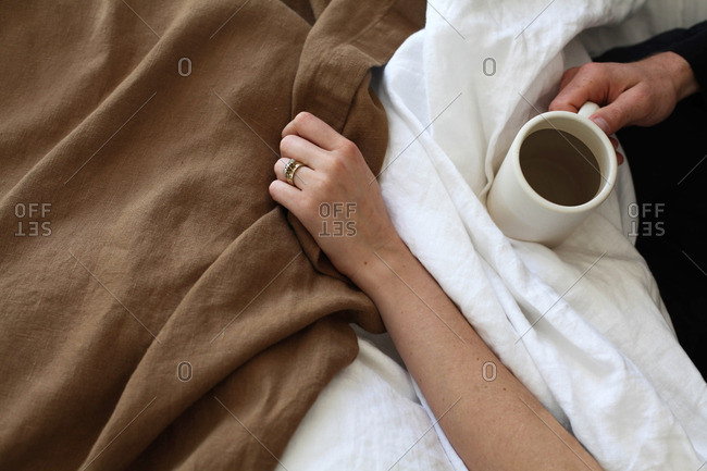 Couple relaxing in bed with cup of coffee