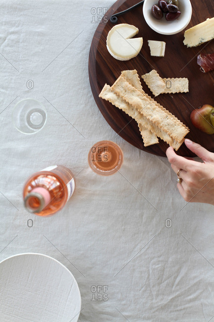 Overhead view of hand taking cracker from tray of charcuterie