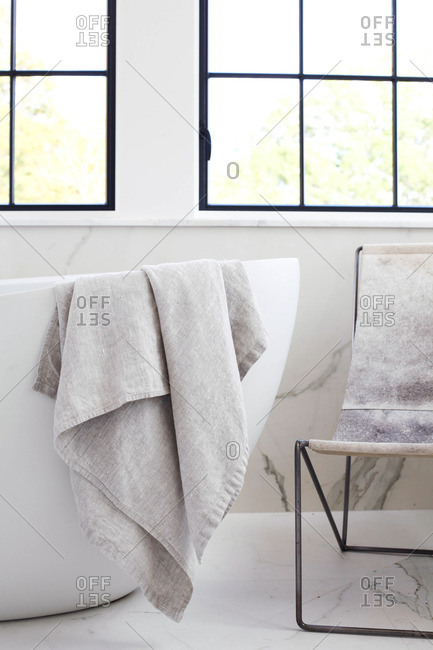 Towel draped over the edge of modern bathtub
