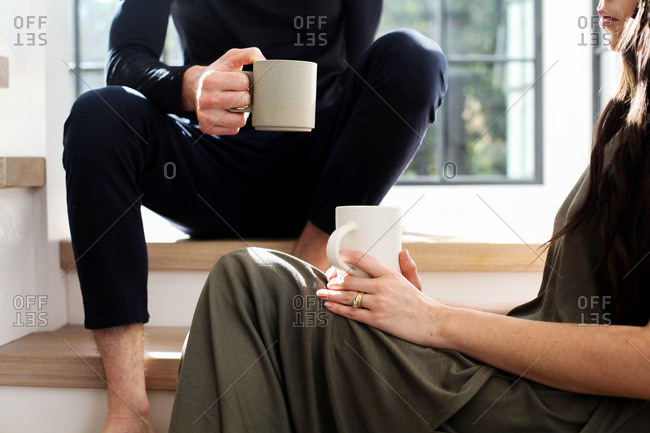 Couple sitting on steps with morning cup of coffee