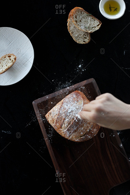 Food stylist sprinkling flour on loaf of bread