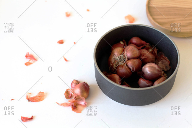 Shallot skins with bowl of shallots on table