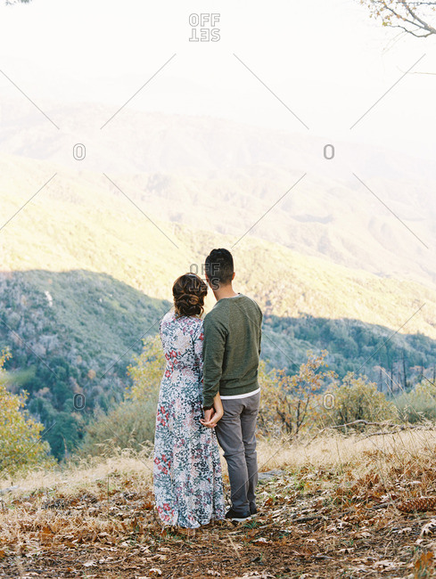 Back view of couple standing on hillside overlooking valley