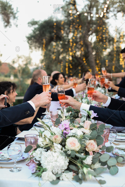 Wedding guests toast with glasses of champagne at reception