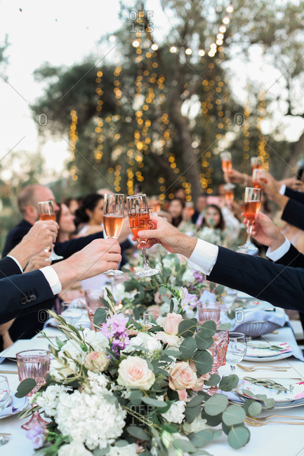 People toast with glasses of champagne at wedding banquet
