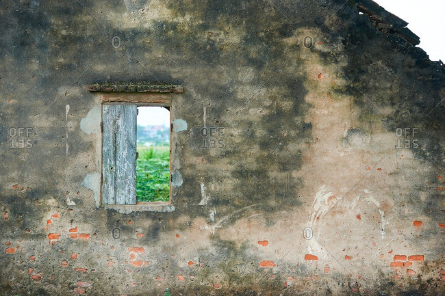 View of countryside through window of ruined house