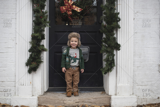Boy at Christmas decorated front door