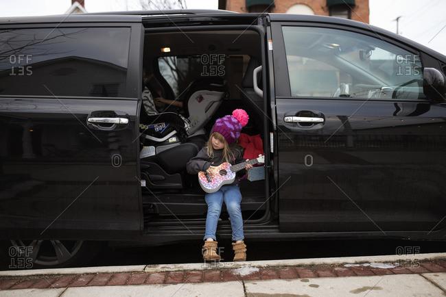 Girl in van door playing guitar