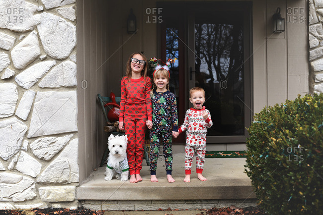 Kids in Christmas pajamas on porch
